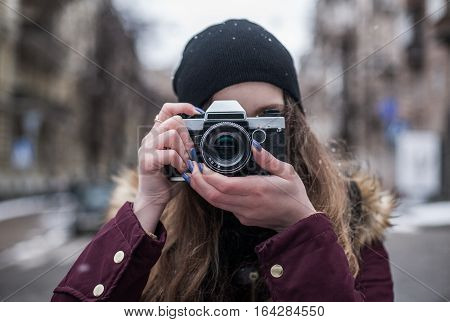 Hipster girl photographer with retro camera taking photo on city street at winter
