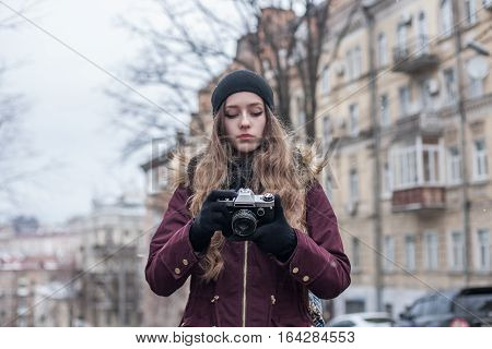 Hipster girl tourist with retro camera taking photos on city street