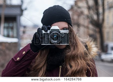 Hipster girl photographer with retro camera taking photo on city street