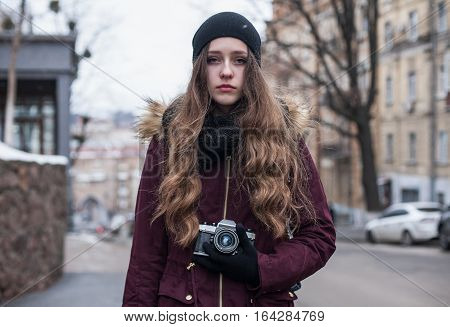 Tired hipster girl traveler with retro camera standing on city street