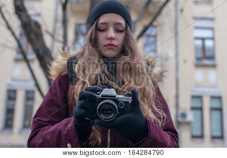 Hipster girl traveller with retro camera taking photo on city street
