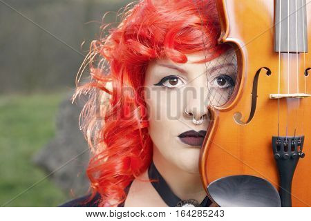 Redhead Woman Playing Violin Outdoors.