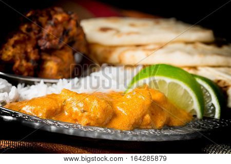 Closeup of dinner plate featuring chicken korma rice pakoras and nan bread.