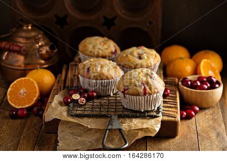 Orange cranberry muffins with orange zest on a cooling rack in dark rustic setting