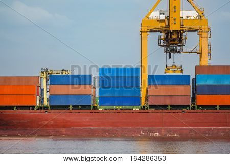 many containers on the truck bulk carriers and yellow crane harbor quayside