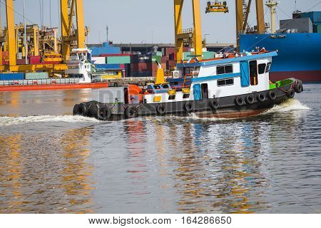 tugboat assisting bulk cargo ship to harbor freight and yellow crane