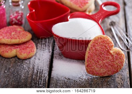 Baking cookies for Valentines day, sugar in red heart shaped measuring cups