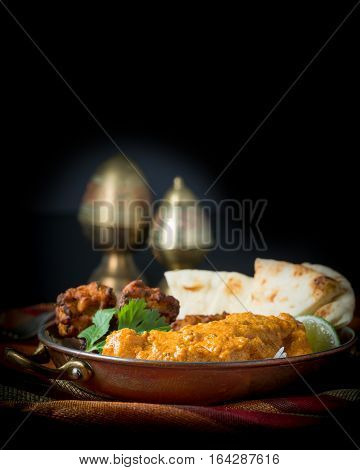 Indian meal consisting of chicken korma rice pakoras and nan bread.