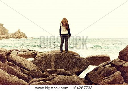 Girl standing on rock. Woman suffering from fear loneliness depression abuse addiction