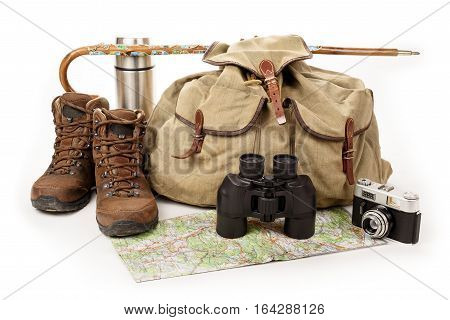 Hiking equipment shoes and backpack on white background