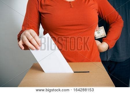 adult woman casting her vote while getting some cash us dollars from a guy standing behind her.