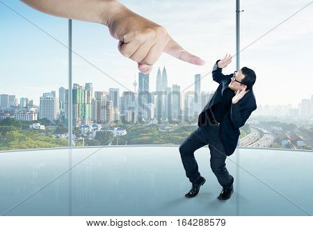 A scared businessman full-height in a scare pose and a giant hand pointing at him on the office background. Business and management. Employment issues. Getting fired. Being told off.