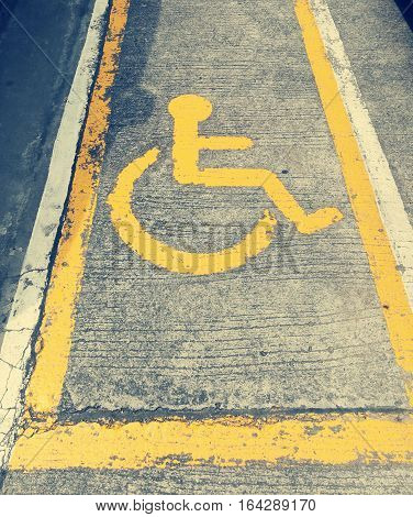 Wheelchair sign on concrete floor indicates route for people on wheelchair.