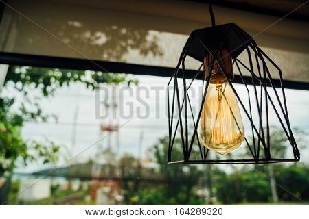 Incandescent lamps in a modern cafe on the background of the generator power plant with wires and pole. Edison lamp.
