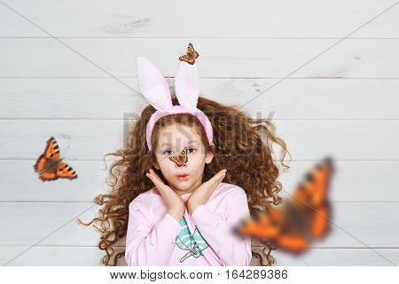 Surprised little girl wearing bunny ears lying on light wooden floor on Easter Holiday. Spring butterfly on the nose.