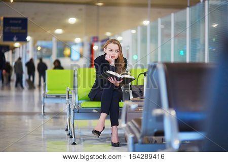 Woman In International Airport Terminal, Reading Book