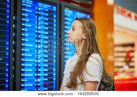 Young Woman In International Airport Looking At The Flight Information Board