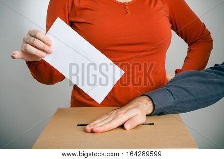 adult man putting his hand over a ballot box, not allowing another person to cast her vote