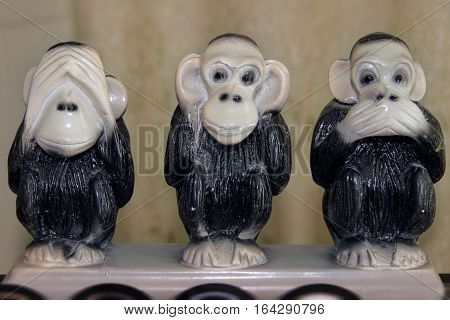 Three funny monkey statues in various fun poses