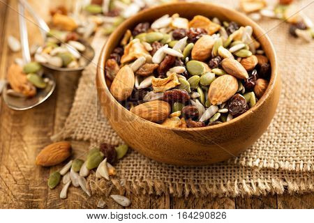 Dried fruit and nuts trail mix with almonds, raisins, seeds and apples in a wooden bowl