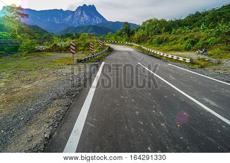 Open tar road with view of mountain landscape.