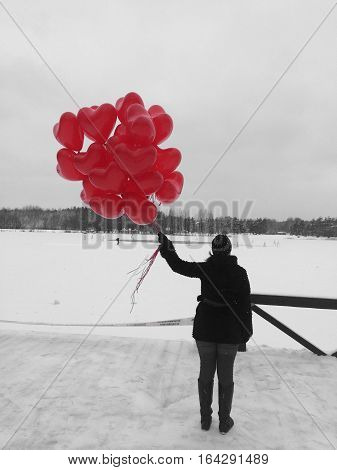 Lady standing in winter with red baloons next to the lake.