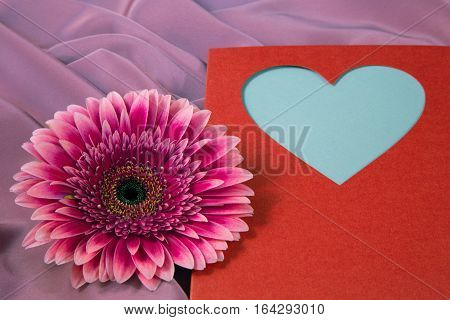 One Gerbera Flower On A Background From Silk  Fabric