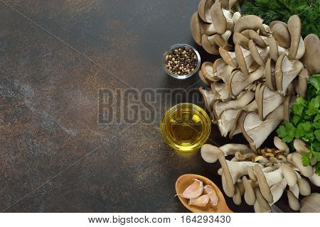 Raw oyster mushrooms on a brown background