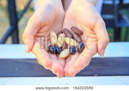 Closeup to multivitamin tablets on two hands of pretty women or girl.