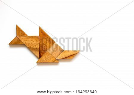 Wooden tangram as sawfish shape on white background