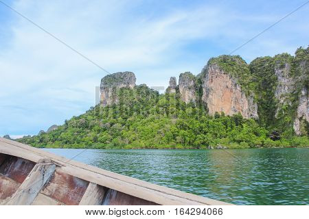 Some part of Long tail boat with rock mountain and forest on the background.