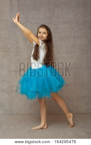 Teen ballerina in a blue tutu with long hair standing in the dance pose