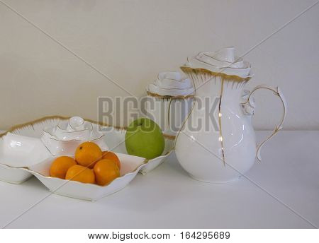 white bowl with tangerines and apples on the kitchen white table