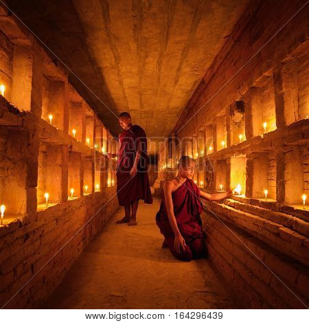 Young Buddhist Monks are lighting candles in mandalay historical park Bagan Mandalay Myanmar
