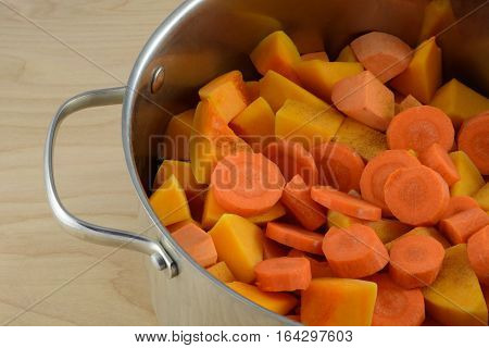 Soup preparation with chopped carrots, butternut squash, yams. and spices in large soup pot