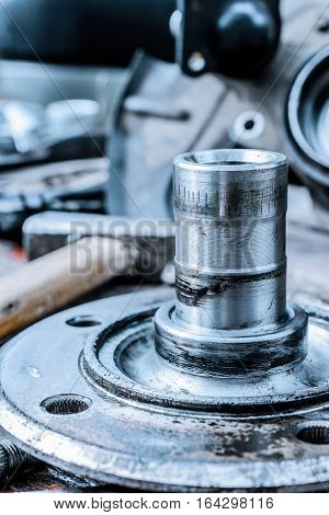 Car hub axis. Abstract industrial background. Old, oiled wheel hub lies on a wooden table.