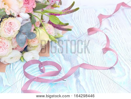 Valentine's Day. Valentine Gift. Satin ribbon in Heart shape and bouquet of flowers on blue wooden background. Beautiful Valentine card art design