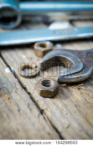 On weathered old wooden surface lie the old, oily wrenches. Near scattered old rusty nuts.
