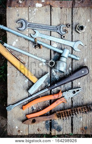 Old hand tools scattered on the wooden surface, overhead view.
