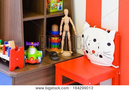 Fragment Interior of modern children's room with red furniture and toys