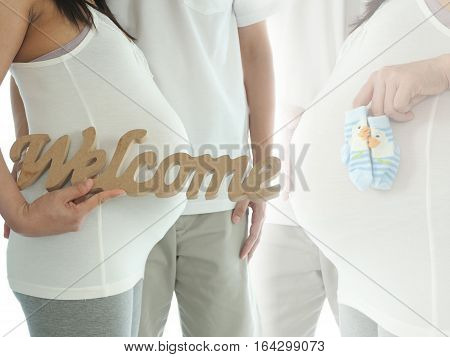 Pregnant Woman With Husband Holding Welcome Message For Incoming Baby Isolated On White Background.