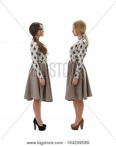 Side view full length shot of  young women wearing high heels and same dresses standing on white isolated studio background and looking at each other