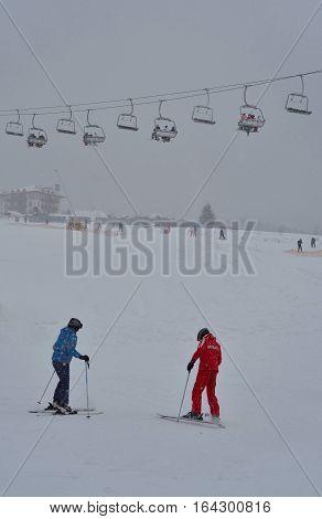 Ski instructor with skiers in ski school on mountain slopes of ski resort