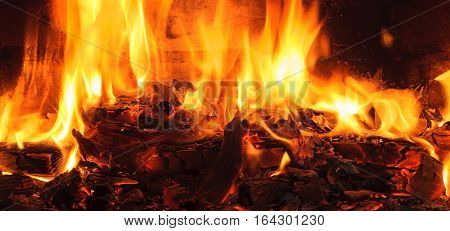 Firewood beautifully lit in the fireplace. burning log and fire