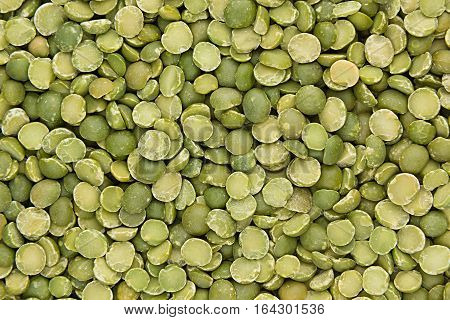 Green dry purified peas closeup top view background. Healthy protein food.