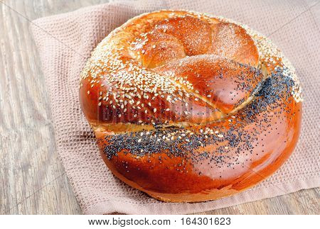 Braided bun sprinkled with poppy seeds and sesame seeds on a old wooden table