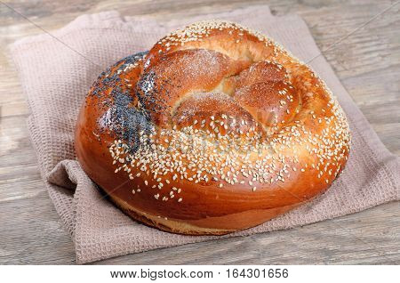 White bread with poppy seeds and sesame seeds on a old wooden table