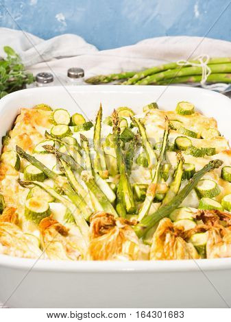 Home made asparagus lasagna casserole with zucchini, ricotta, mozzarella cheese and marjoram herb in a ceramic tin on wooden table. Rustic spring baked one plate food