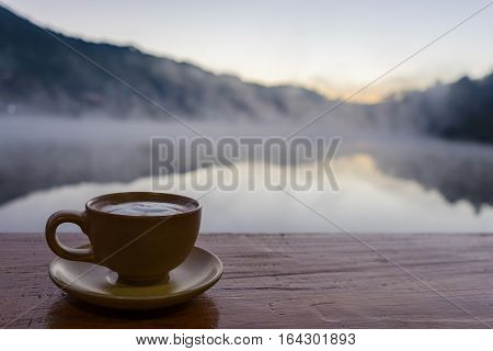 A cup of hot coffee put on old wood wooden table background.Vintage tone with copy space. View of mist over lake at sunrise.