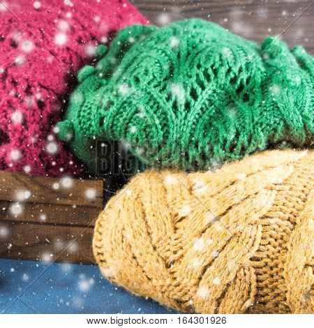 Winter womans woolen sweaters. Knitted girls clothing. Colorful pullovers on wooden background. Cozy clothes for the season. Square image. Falling snow effect